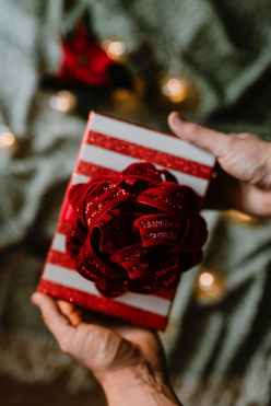 person holding red and white gift box with ribbon bow